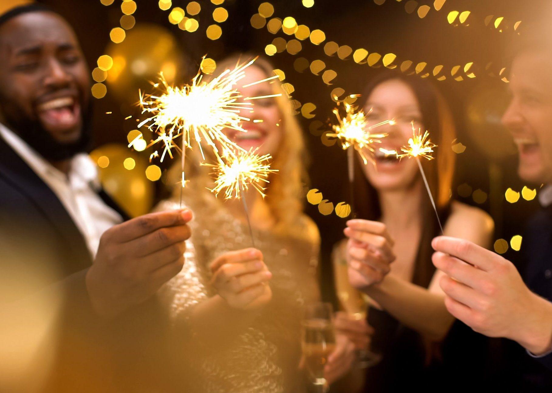 Amis riant et tenant des bougies scintillantes au cours d'une fête
